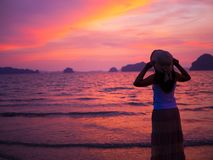 Silhouette of woman wearing hat with open arms under the sunrise. Near the sea. Summer concept Royalty Free Stock Photos
