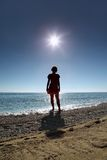 Silhouette of woman which stands on beach in water stock photos