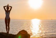 Silhouette woman yoga on the beach at sunrise. Woman is practicing yoga at sunset on sea shore. Calm and self control stock image