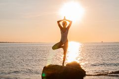 Silhouette woman yoga on the beach at sunrise. Woman is practicing yoga at sunset on sea shore. Silhouette woman yoga on the beach at sunset. Woman is practicing royalty free stock photos