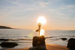 Silhouette woman yoga on the beach at sunrise. Woman is practicing yoga at sunset on sea shore. Calm and self control royalty free stock image