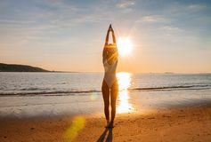 Silhouette woman yoga on the beach at sunrise. Woman is practicing yoga at sunset on sea shore. Calm and self control stock photos