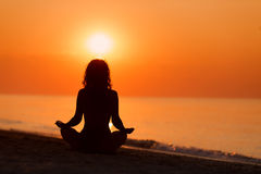 Silhouette of woman in yoga lotus meditation position front to s Stock Images