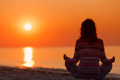 Silhouette of woman in yoga lotus meditation position front to s Stock Image