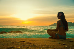 Silhouette woman yoga on the sea beach at sunset Stock Photography
