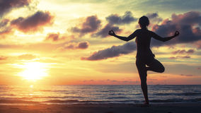 Silhouette of a woman yoga on sea sunset. Stock Photo