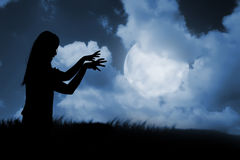 Silhouette of woman zombie walking under full moon. Halloween concept Stock Photos