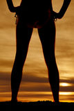 Silhouette of womans legs back hands on hips Stock Photo