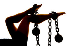 Silhouette of womans legs with ball and chain Stock Photos