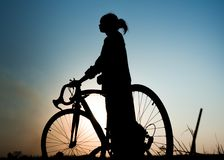 Silhouette women with a bicycle. Silhouette of young woman with bicycle outdoor Royalty Free Stock Images