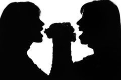 Silhouette of women with hamburger one for two. Black and white silhouette of women with one double hamburger biting fast food from different sides stock images