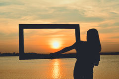 Silhouette of women holding frame Stock Images