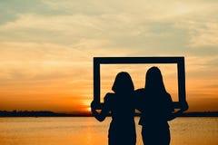 Silhouette of women holding frame Stock Photos
