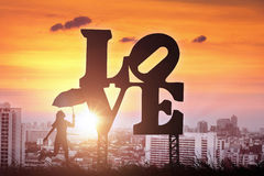 Silhouette of women holding umbrella valley on love sign  Royalty Free Stock Photography