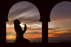 Silhouette of a women praying during sunset Royalty Free Stock Photo