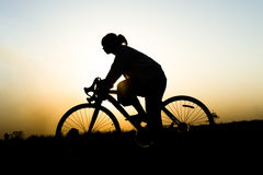 Silhouette of a women. Silhouette of young woman cyclist on sunset sky with riding along the prairie at yellow evening horizon sea yellow sunset heaven Royalty Free Stock Photo