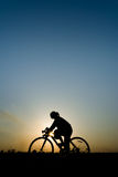 Silhouette of a women. Silhouette of young woman cyclist on sunset sky with riding along the prairie at yellow evening horizon sea yellow sunset heaven Stock Photography
