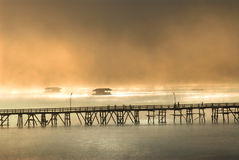 Silhouette of the wooden bridge in the mist. Stock Photos