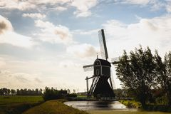 Silhouette of a wooden hollow post mill in a Dutch polder. The Wingerdse Molen near the village of Bleskensgraaf in South Holland was built around 1513, later stock images