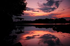A silhouette of a wooden hut by a river during sunset in Terengganu, Malaysia Stock Photo