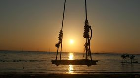 Silhouette of wooden swing seat hanging on coconut tree by the sea on tropical beach during amazing sunset and shining. The sun on the background. slow motion stock video