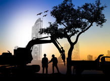 Silhouette worker with Loaders and trucks in a building site ove Royalty Free Stock Photography