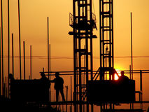 Silhouette of workers in setting sun stock images