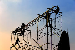Silhouette of workers at Twilight Stock Photos