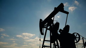 Silhouette of working oil pump on a background of blue sky and white clouds. stock video footage