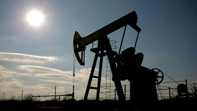 Silhouette of working oil pump on a background of blue sky and white clouds. stock video