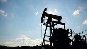 Silhouette of working oil pump on a background of blue sky and white clouds. stock footage