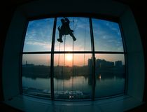 Silhouette working outside the window. At the height of the background of the morning city royalty free stock photos