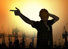 Silhouette of workman dancing happy emulating with hard hat pop star pose celebrating workday is over  on harbour cranes royalty free stock photography