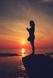 Silhouette yoga girl by the beach at sunrise doing standing pose Royalty Free Stock Image