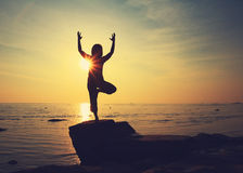 Silhouette yoga girl by the beach at sunrise doing standing pose Stock Photos