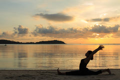 Silhouette yoga girl at sunrise on the beach Royalty Free Stock Photography