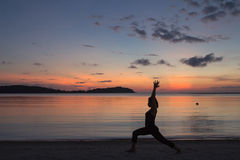 Silhouette yoga girl at sunrise on the beach Royalty Free Stock Images