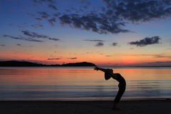Silhouette yoga girl at sunrise on the beach Stock Photo