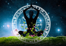 Silhouette of yoga pose against night sky. Silhouette of person in seated yoga pose covered in flowers illustrated with characters and flowers against night Stock Photo