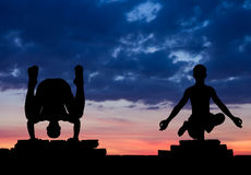 Silhouette in yoga pose on a brick wall. Royalty Free Stock Photos