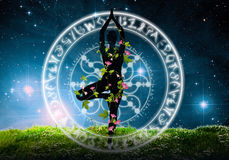 Silhouette of yoga position. Silhouette of persona standing in yoga position inside graphic circle in green field with flowers against starry night sky Stock Images