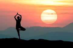 Silhouette Yoga practitioner during twilight sunset meditation with Omega sunset or Inferior-Mirage Sunset. Silhouette Yoga practitioner during the twilight Royalty Free Stock Images