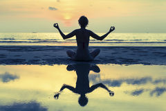 Silhouette of yoga woman meditating on the ocean beach. Royalty Free Stock Photos