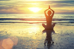 Silhouette of yoga woman meditating on the ocean beach. Fitness. Royalty Free Stock Images