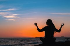 Silhouette of yoga woman meditation on the ocean . Silhouette of yoga woman meditation on the ocean during amazing sunset Royalty Free Stock Photography