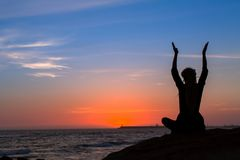 Silhouette of yoga woman meditation on the ocean. Silhouette of yoga woman meditation on the ocean during amazing sunset Royalty Free Stock Photos