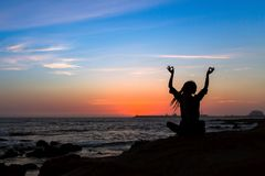 Silhouette of yoga woman meditation on the ocean. During sunset Royalty Free Stock Photo