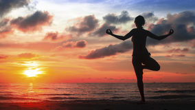 Silhouette yoga woman on ocean beach at magic sunset. Royalty Free Stock Photo