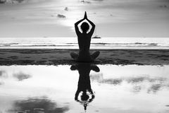 Silhouette of yoga woman on sea coast. Contrasting black and white photo Stock Photo