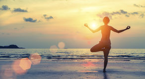 Silhouette of yoga woman on sea sunset Meditation. Stock Photography